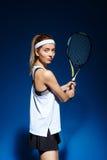 Женский теннисист с ракеткой готовой для того чтобы ударить шарик Стоковое Изображение