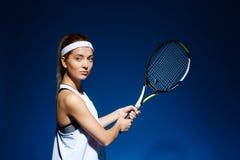 Женский теннисист с ракеткой готовой для того чтобы ударить шарик Стоковая Фотография
