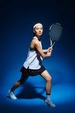Женский теннисист с ракеткой готовой для того чтобы ударить шарик Стоковые Изображения