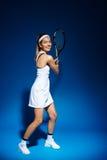 Женский теннисист с ракеткой готовой для того чтобы ударить шарик Стоковые Изображения RF