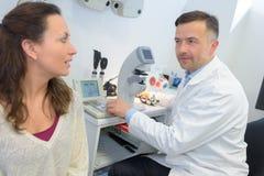 Женский терпеливый взаимодействовать с optometrist в клинике офтальмологии стоковые изображения rf