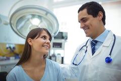 Женский терпеливый взаимодействовать с доктором во время посещения стоковые изображения