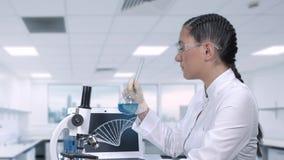 Женский техник лаборатории исследует лечение для рака Женский ученый проводит клинические испытания Научное видеоматериал
