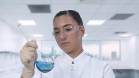 Женский техник лаборатории рассматривает голубую жидкость в стеклянной склянке и проводит клиническое исследование в научной лабо видеоматериал