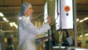 Женский техник проводит продукцию с особенным оборудованием акции видеоматериалы