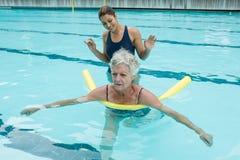 Женский тренер помогая старшей женщине в бассейне Стоковое Изображение RF