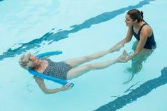 Женский тренер помогая старшей женщине в бассейне Стоковые Изображения RF