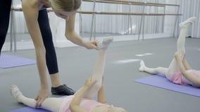 Женский тренер школы держит ногу в правильном положении девушки на циновке сток-видео