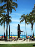 Женский туристский взгляд на статуе герцога Kahanamoku держа leis на Wa Стоковые Фотографии RF