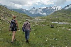 Женский туристский идти через гористые ландшафт и пейзаж на популярном туристском походе около Bokonbayevo, Кыргызстана стоковое фото rf