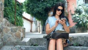 Женский турист ищет информацию на вебсайте через мобильный телефон о истории этот красивый старый городок сток-видео