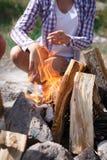 Женский турист разжигая для того чтобы начать лагерный костер, конец-вверх костра Человек разжигает огонь Пожар в природе Костер  Стоковое Фото