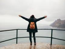 Женский турист с ее оружиями протягивал смотреть океан стоковые изображения rf