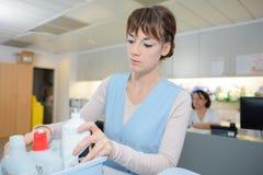 Женский уборщик в форме подготавливая очищая оборудование в больнице стоковое изображение