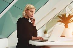 Женский умный менеджер работая на портативном компьютере пока она имеет переговор мобильного телефона стоковые фото