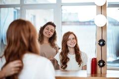 Женский усмехаться парикмахера и девушки, смотря в зеркале в салоне красоты Стоковое Изображение RF