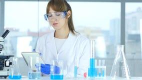 Женский ученый в документах чтения лаборатории, обработка документов результата исследования Стоковые Изображения