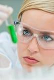 Женский ученый исследования женщины с пробиркой в лаборатории стоковые фото