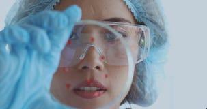 Женский ученый смотря образцы от ее эксперимента акции видеоматериалы
