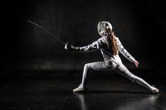 Женский фехтовальщик на черной предпосылке стоковая фотография