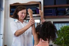 Женский физиотерапевт давая массаж руки к пациенту девушки Стоковое фото RF