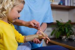 Женский физиотерапевт давая массаж руки к пациенту девушки Стоковое Изображение