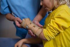 Женский физиотерапевт давая массаж руки к пациенту девушки Стоковая Фотография RF