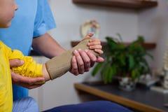 Женский физиотерапевт давая массаж руки к пациенту девушки Стоковые Изображения RF