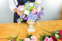 Женский флорист на работе используя аранжировать делая красивый искусственный жилет букета на цветочном магазине, деле, продаже и стоковая фотография