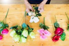 Женский флорист на работе используя аранжировать делая красивый искусственный жилет букета на цветочном магазине, деле, продаже и стоковая фотография rf