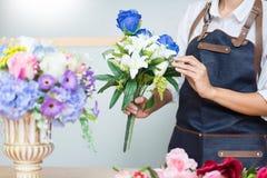 Женский флорист на работе используя аранжировать делая красивый искусственный жилет букета на цветочном магазине, деле, продаже и стоковое фото rf