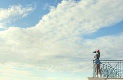Женский фотограф в красной крышке с камерой стоит на балконе напротив голубого неба с облаками Женщина фотографирует небо Стоковые Фото