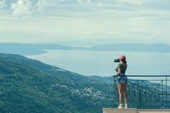 Женский фотограф в красной крышке с камерой стоит на противоположности балкона греческого города Volos на заходе солнца Volos Гре Стоковые Изображения