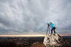 Женский фотограф с камерой на треноге на большом утесе Стоковые Фотографии RF