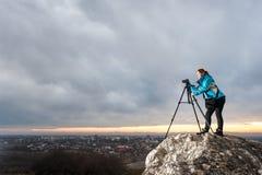 Женский фотограф с камерой на треноге на большом утесе Стоковое Изображение