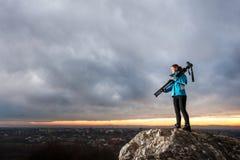 Женский фотограф с камерой на треноге на большом утесе Стоковое фото RF