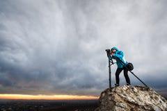 Женский фотограф с камерой на треноге на большом утесе Стоковое Изображение RF