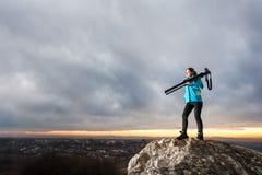 Женский фотограф с камерой на треноге на большом утесе Стоковые Изображения