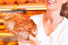 Женский хлебопек в ее хлебопекарне Стоковые Изображения RF