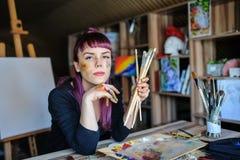 Женский художник с фиолетовыми волосами и пакостными руками стоковое фото rf