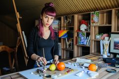 Женский художник с фиолетовыми волосами и пакостными руками стоковое фото