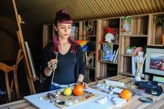 Женский художник с фиолетовыми волосами и пакостными руками стоковые фото