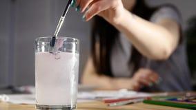 Женский художник держа кисть, окунающ внутри для того чтобы покрасить и намочить видеоматериал