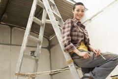 Женский художник сидя на лестнице на месте производства работ Стоковые Изображения RF