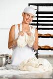 Женский хлебопек держа тесто на таблице Стоковое Изображение