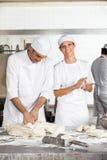 Женский хлебопек делая шарики теста мужским коллегой Стоковое Изображение