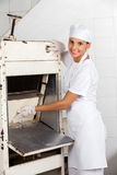 Женский хлебопек используя Slicer хлеба на хлебопекарне Стоковые Изображения