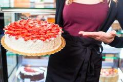 Женский хлебопек представляя торт в кондитерскае Стоковое фото RF