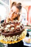 Женский хлебопек представляя торт в кондитерскае Стоковое Фото