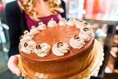 Женский хлебопек представляя торт в кондитерскае Стоковые Изображения RF